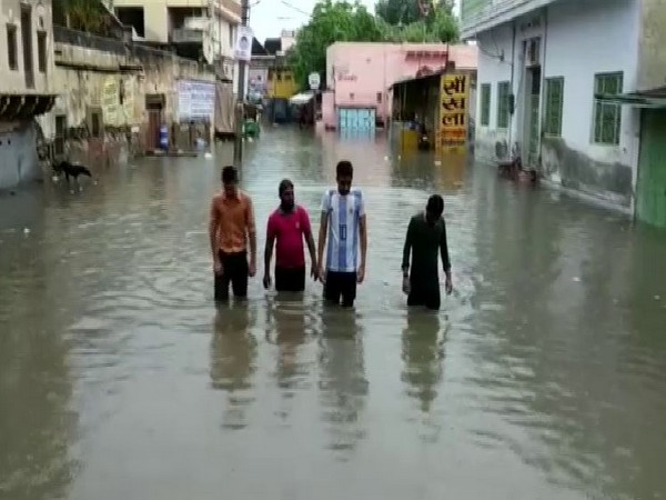 Locals forced them to wade through knee-deep waters triggered by heavy downpour in Churu, Rajasthan (Photo/ANI)