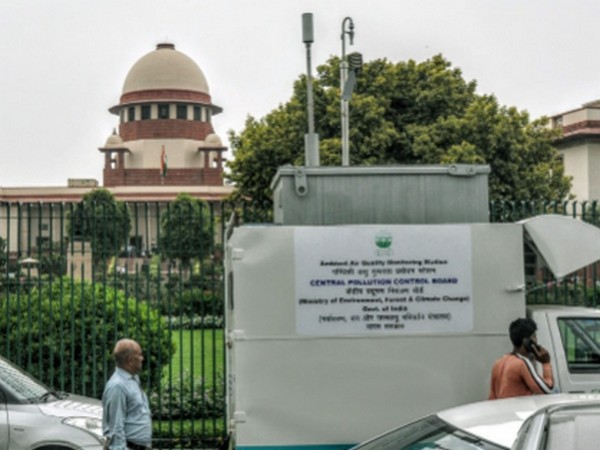 People walking past an Ambient Air Quality Monitoring Station at the Supreme Court in New Delhi (File photo)