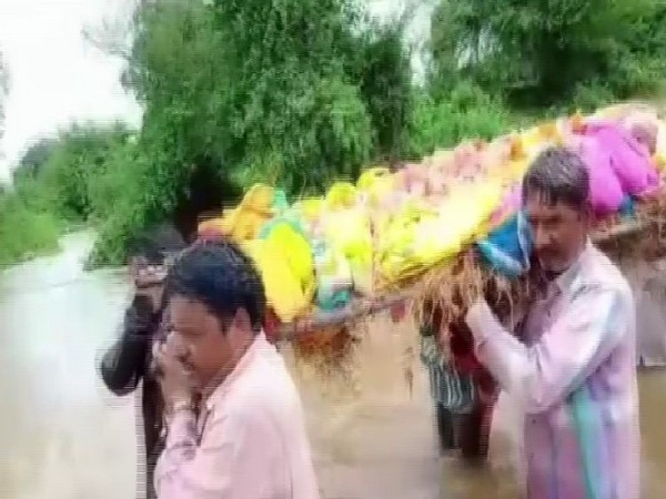 Villagers were forced to take dead body of an elderly woman through flooded drains in Mandsaur. Photo/ANI