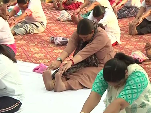Union Minister Smriti Irani in brown kurta performing a yoga asana in Dwarka, New Delhi [Photo/ANI]