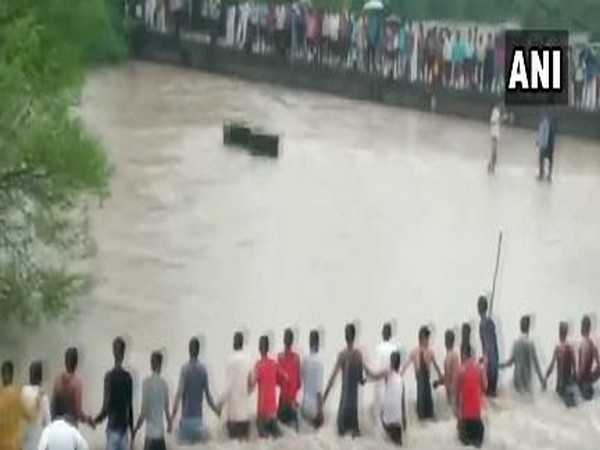 Locals formed a long human chain to rescue two people who were washed away in an overflowing stream in Indore?s Gautampura. (Photo/ANI)