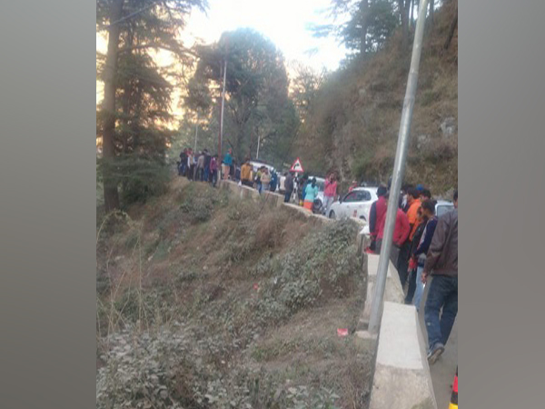 People gathered at the spot where a car fell into a gorge at Dobata area of Barkot town on Saturday.
