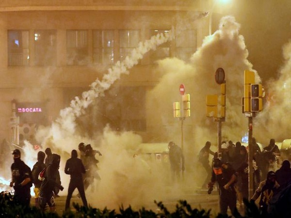 Catalan demonstrators throw back to the police a tear gas canister officer during Catalonia's general strike on Thursday