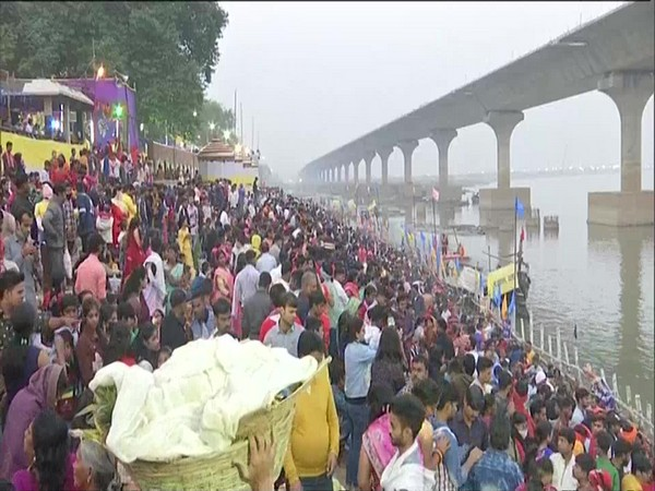 Devotees offer arghya to the rising sun at Patna College ghat on the last day of Chhath Puja on Saturday. (Photo/ANI)