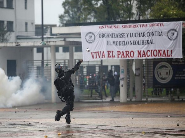 A riot police officer throws a tear gas canister during a protest in Bogota.