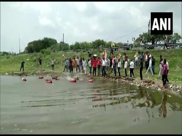 Congress workers throwing gas cylinders in Dewas' Meetha Taalab. (Photo/ANI)