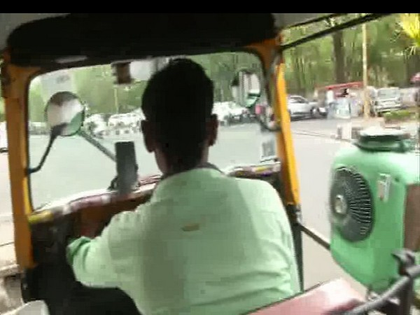 Ramnarayan, an auto driver driving his auto with his self-made cooler fixed on his right side.