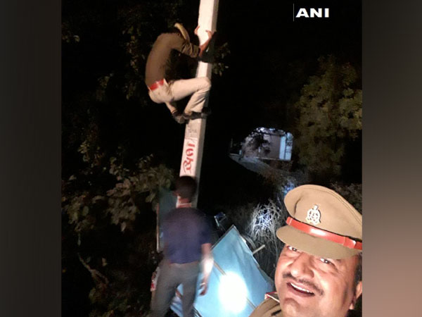 Sub-inspector clicking photo with constable who climb up the electricity pole to remove posters in Unnao, Uttar Pradesh.