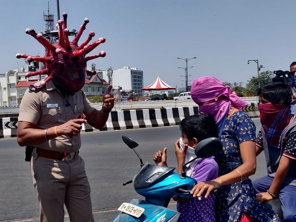 Inspector Rajesh Babu using the Corona helmet while talking to commuters in Chennai on Saturday. Photo/ANI