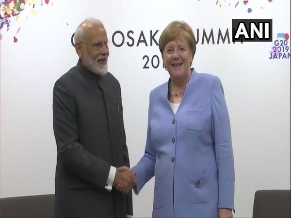 Prime Minister Narendra Modi shaking hands with German Chancellor Angela Merkel on Friday