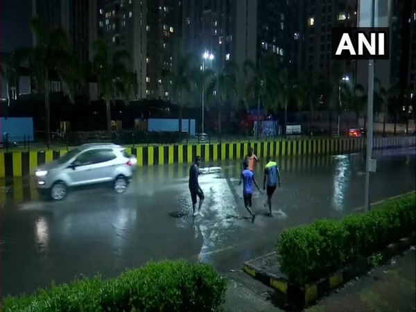 People play in the rain outside as heavy showers lash different parts of the city. Photo/ANI
