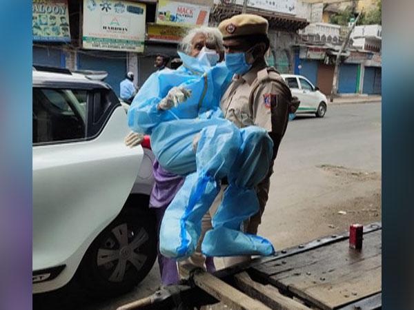 Delhi Police constable Kuldeep Singh carrying Shaila D'Souza to vaccination centre.