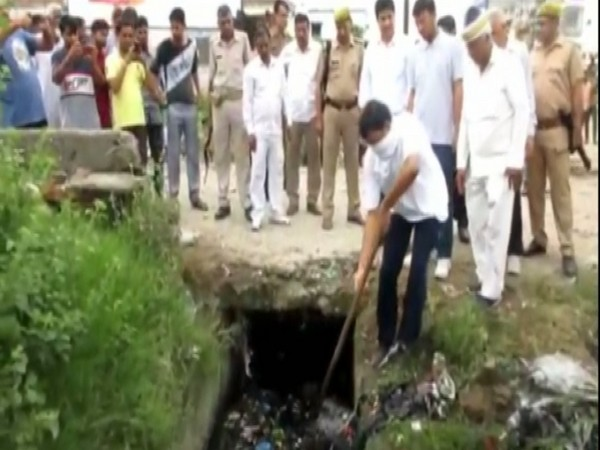 District Magistrate Aunjaneya Kumar Singh seen cleaning drains in Rampur on Saturday. Photo/ANI