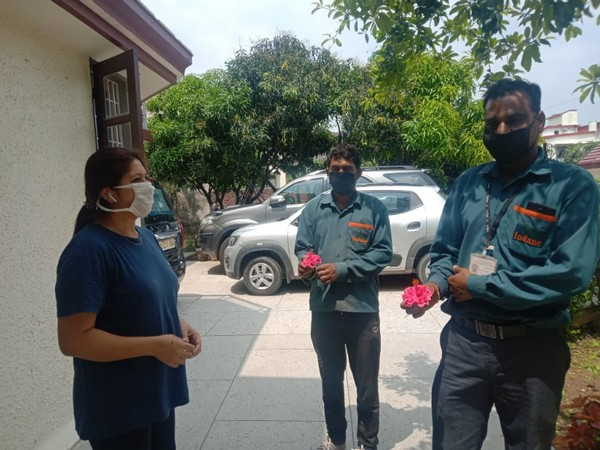 Deepti Rawat, Vice-Chairperson of Uttarakhand Higher Education, giving rose to the two LPG delivery boys. Photo/ANI