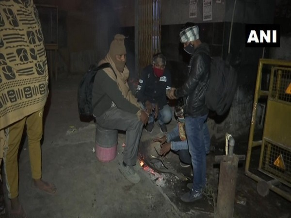 People sit near the fire to protect themselves from cold in Delhi's Anand Vihar (Photo ANI)