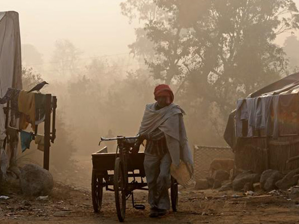 A man pulls a handcart on the banks of the Yamuna river on a foggy winter morning in New Delhi