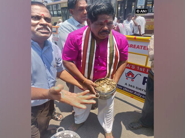 Kuppalji Devadoss carrying metal pot filled with coins worth Rs 25000 in Chennai on Monday.