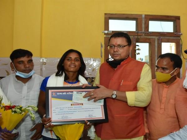 Pushkar Singh Dhami felicitating hockey player Vandana Katariya. (Photo/ANI)