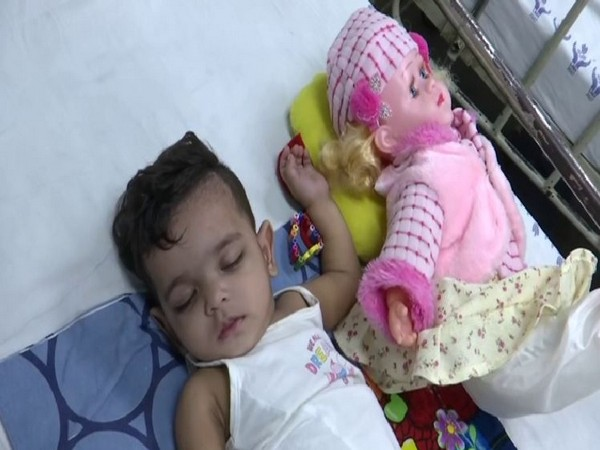 The 11-month-old Zikra receiving treatment with her doll at Lok Nayak Hospital in Delhi. Photo/ANI