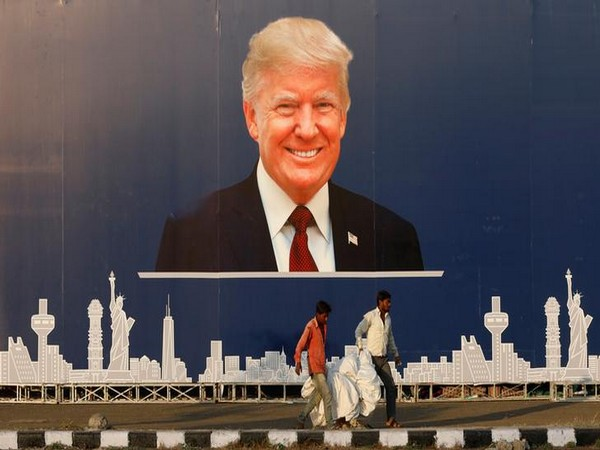 Workers walk past a hoarding of U.S. President Donald Trump in Ahmedabad