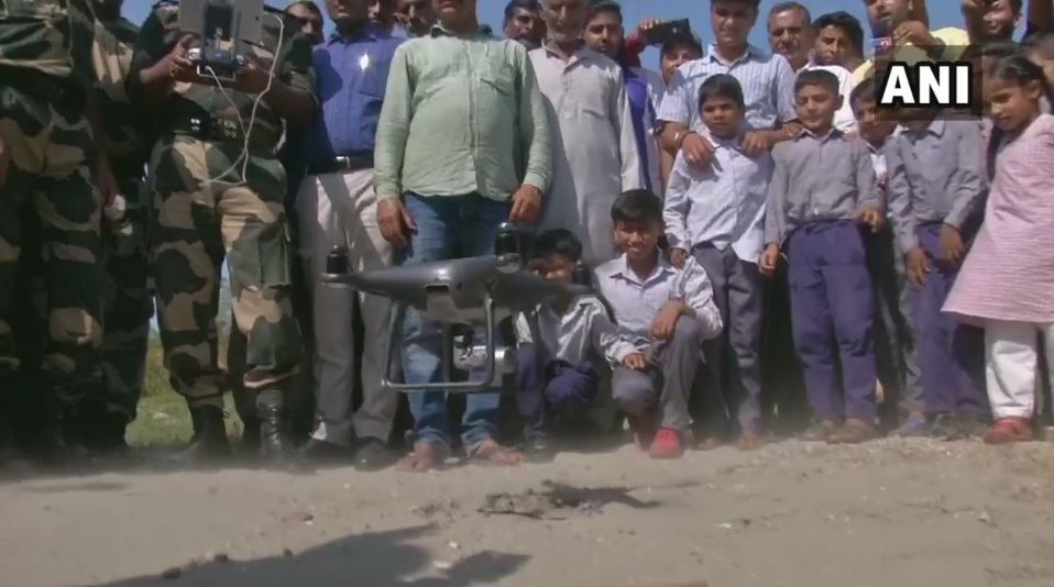 Children watch in awe as BSF demonstrates application of a drone to the locals in Jammu. Photo/ANI