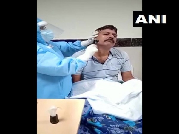 Healthcare worker at Odisha's MKCG Medical College and Hospital shaving beard of a COVID patient (Photo/ANI)