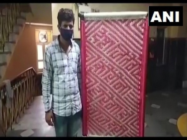 Cot weaver Shravan shows a cot made by him with an awareness message. [Photo/ANI]