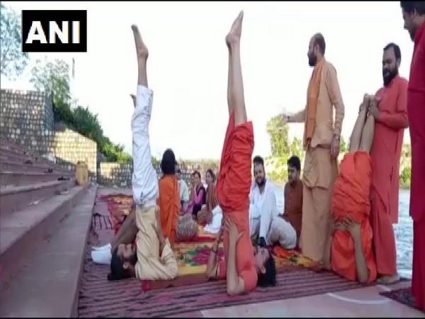 Saints perform Yoga on the banks of river Ganga in Haridwar. (Photo/ANI)