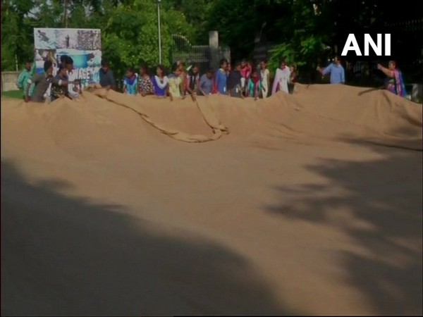 Volunteers, along with the nine visually challenged people, sewing the world's largest jute bag in an attempt to enter the Guinness World Record. Photo/ANI