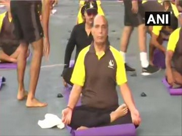 Defence Minister Rajnath Singh performing yoga onboard INS Vikramaditya on Sunday morning. (Photo/ANI)