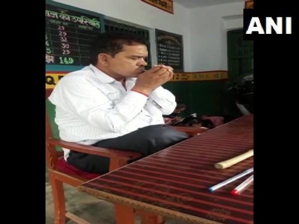 Teacher smoking inside a classroom of a primary school in Mahmudabad. Photo/ANI