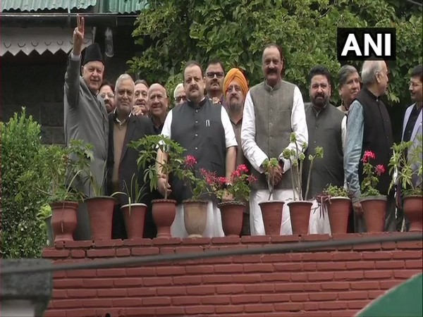 Farooq, clad in a grey suit, looked hale and hearty. He made a peace sign as he stood with the visiting party leaders for a photograph. (Photo/ANI)