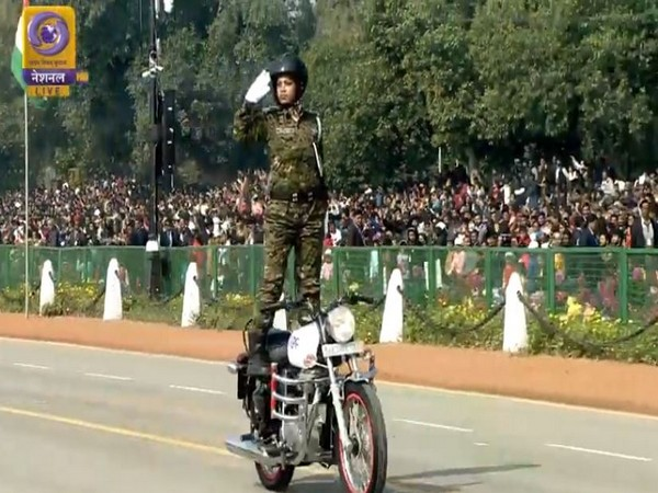 Inspector Seema Nag, salutes standing on top of a moving motorcycle