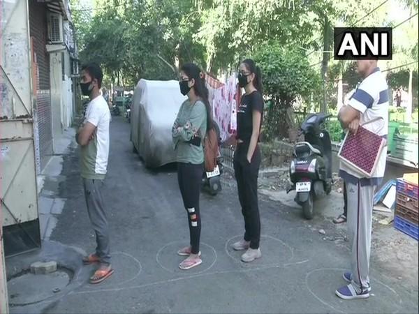People in Noida, Uttar Pradesh practice social distancing amid COVID-19 outbreak on Wednesday.