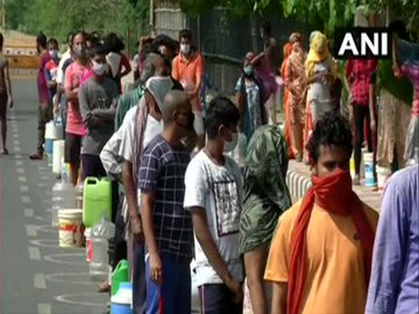 People in Chilla village line up to collect drinking water from DJB tankers amid coronaLockdown. Photo/ANI