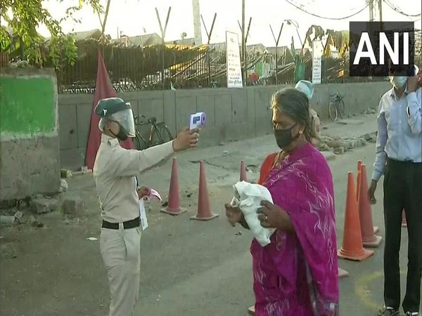 Police checking temperature of people at Okhla vegetable market. (Photo/ANI)