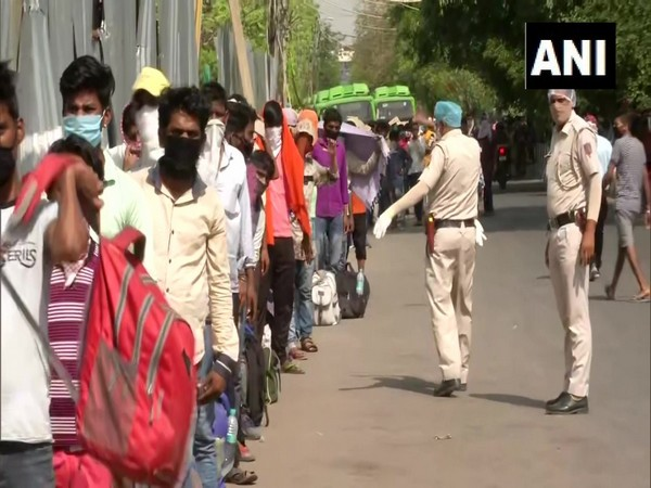 Migrant workers queue outside Lajpat Nagar police station to board buses.