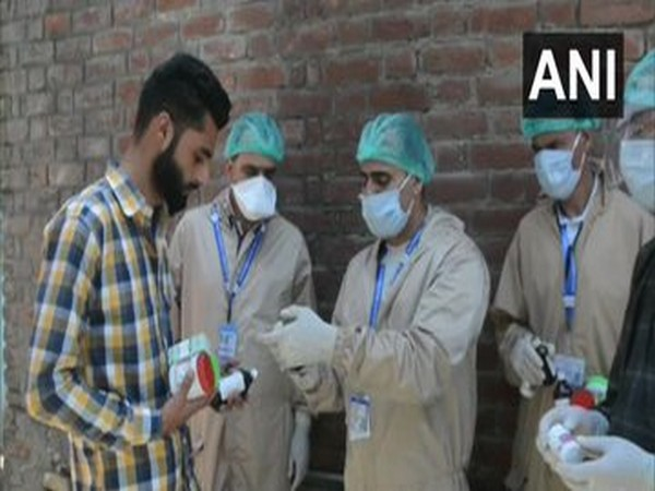 Officials of Jammu and Kashmir AYUSH Department distributed immunity booster medicines to the residents in red zones (Photo/ANI)