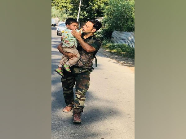 Police carrying the 3-year-old boy to safety in J-K's Sopore.