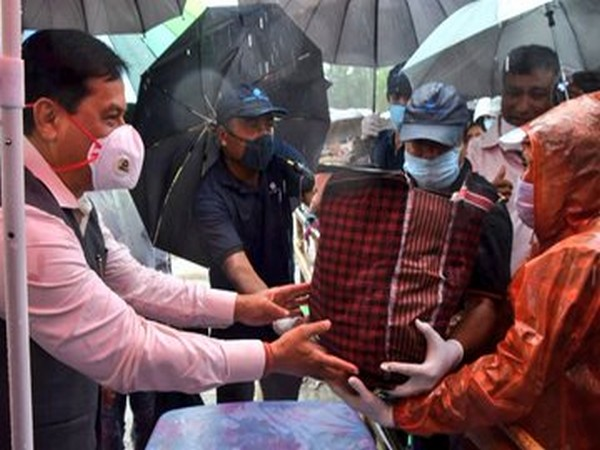 Assam CM Sarbananda Sonowal distributes relief package to needy near Jiadhal river site on Wednesday. [Photo/ANI]