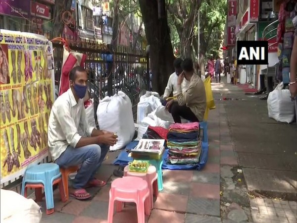Durgesh Kumar, a henna artist in Bangalore waits on the pavement for customers. (Photo/ANI)