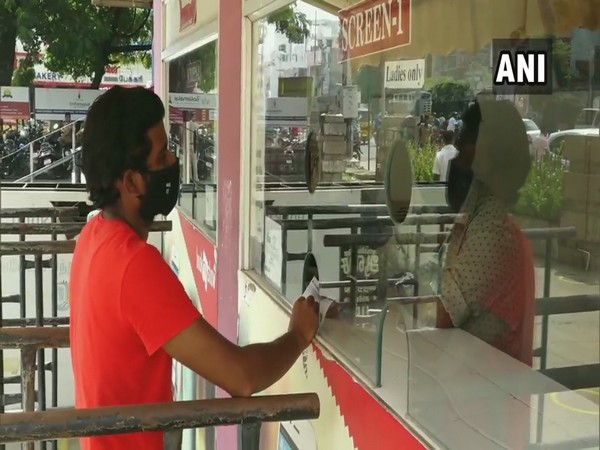 A customer purchasing a ticket in a Madurai movie theatre. (Photo/ANI)