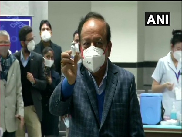 Union Minister Dr Harsh Vardhan holding up a COVAXIN dose (Photo/ANI)