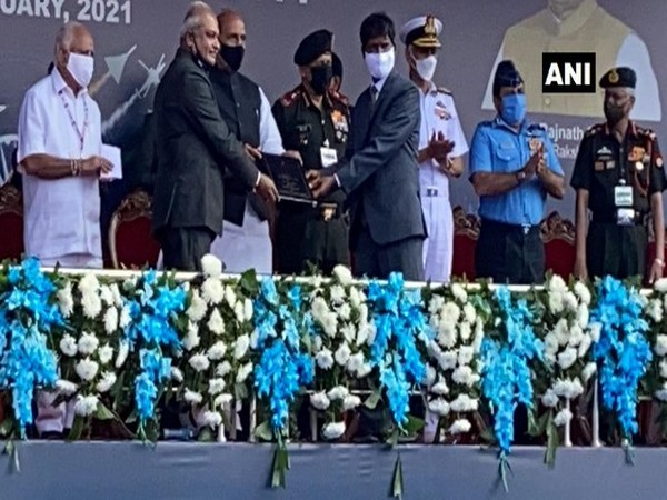 Defence Minister Rajnath Singh presented the Tejas model to HAL chief R Madhavan at the opening ceremony of the Aero India 2021. Photo/ANI