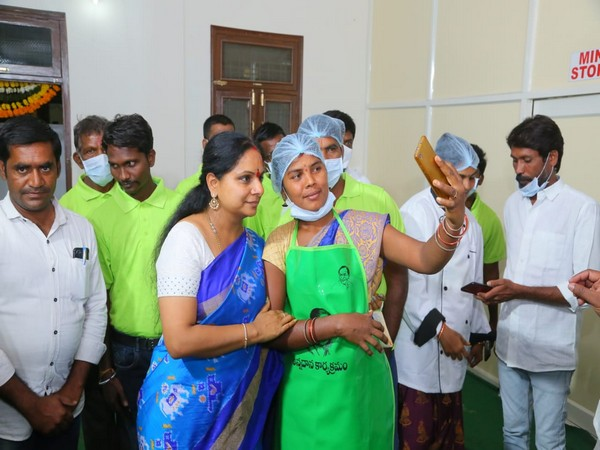 TRS MLC Kavitha Kalvakuntla poses for a selfie with a worker at the inauguration of a free food centre in Telangana's Nizamabad.