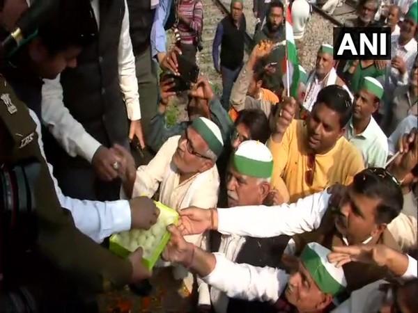 Farmers distributing sweets at Modinagar during Rail roko (Photo/ANI)