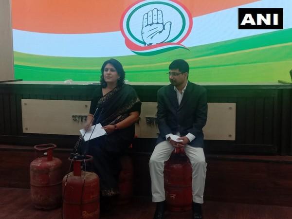 Congress leaders Supriya Shirnate and Vineet Punia sitting on LPG cylinders to address media on Thursday. (Photo/ANI)