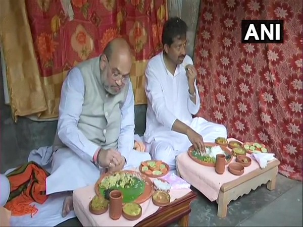 Union Home Minister Amit Shah having lunch at rickshaw puller's home. (Photo/ANI)