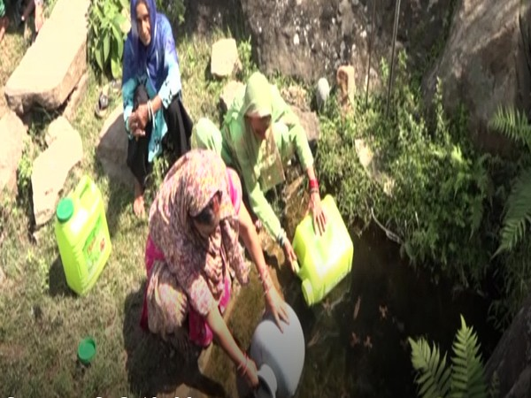 Women are fetching water from a pit in JK's Udhampur. (Photo/ANI)