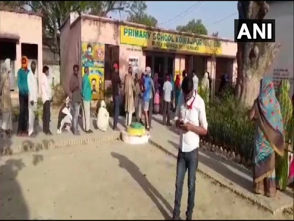 People standing in queue to cast vote for Panchayat polls at Koirajpur Primary School in Varanasi on Monday. (ANI)